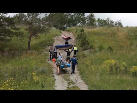 Russia, Siberia 2014: Men carry a rubber boat in the mountain. Tourists