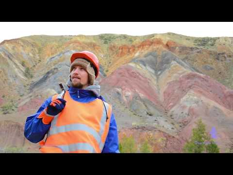 Portrait of a mining engineer, a geologist in the protective reflective vest, gloves and helmet
