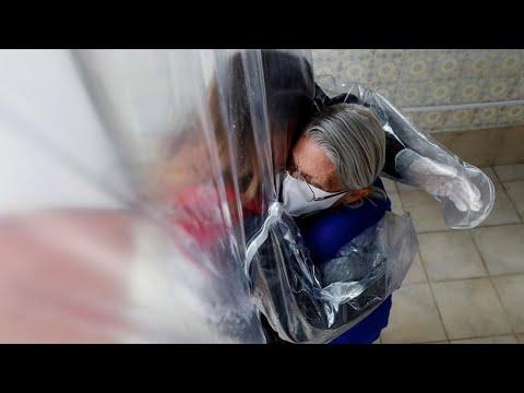 Efectos del coronavirus: Una cortina permite volver a abrazar a los ancianos de una residencia