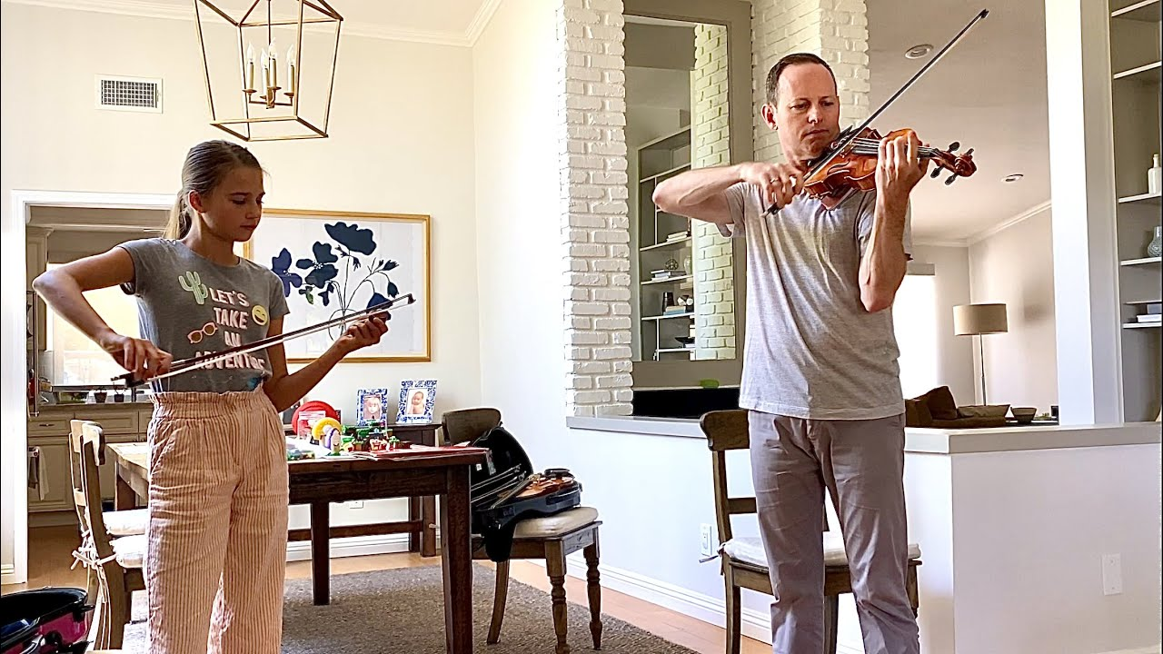 My violin teacher is playing on my violin and testing a new bow