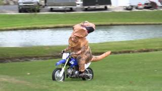 Ryan riding his TTR50 dirt bike in a Jurassic Park T-Rex Tyrannosaurus Costume