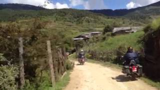 Bhutan riding into a village on a typical road