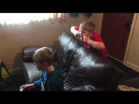 Oliver pulling faces behind Jack's back