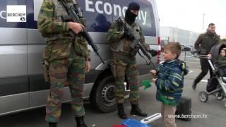 Kind geeft tijdens Berchemse Sinterklaasstoet ook snoepjes aan militairen die luchthaven van Antwerp