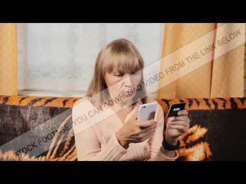Senior woman making online banking by credit card on her mobile phone at home