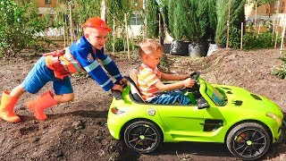 Nikita ride on children's car and stuck in the ground Vlad tows on the tractor