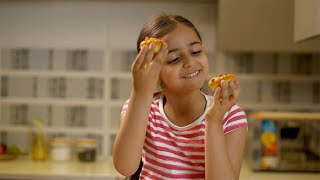Cute little kid girl holding and enjoying tasty cupcakes in the kitchen