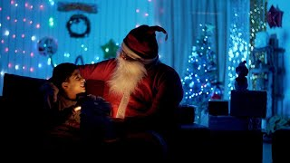 Cute little kid and old Santa opening a magical present in a dark room - Christmas Eve