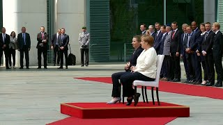 Angela Merkel sits for military honours after being seen shaking three times