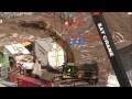 Caterpillar 345BL excavator moving container