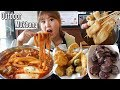 Outdoor Mukbang in Korean tteokbokki restaurant eating noodle tteokboki, odeng, sundae, fried food