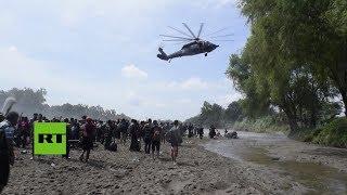 Un helicóptero trata de evitar que los migrantes crucen de Guatemala hacia México