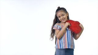 Happy Indian girl holding her red heart toy with a smile on her face - a symbol of love