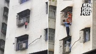 2-year-old dangles by his head out of a window