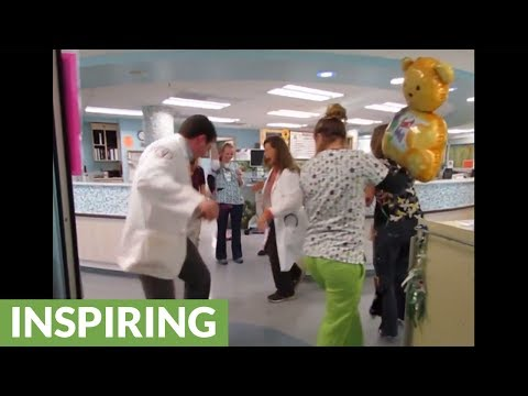 Doctors and nurses dance with sick child