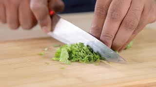 Close up shot of a chef chopping coriander leaves