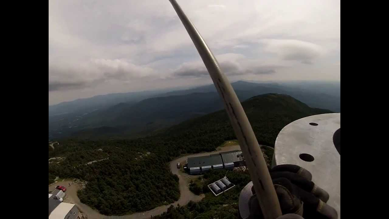 Helicopter mounting a 1 ton TV antenna on top of a tower on top of  a  mt. in Vermont