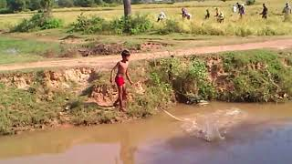Boy with fishnet in countryside, Cambodia