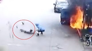 Man rolling on the ground puts out fire on his clothes with the help of a food delivery man