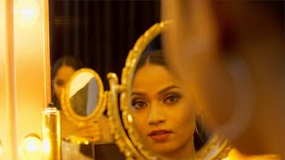 The young lady is done with her party makeup and checking her styling in a golden framed mirror