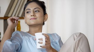Adorable Indian girl holding a coffee mug,  sitting and looking outside the window