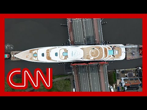 Huge superyacht squeezes through narrow canals
