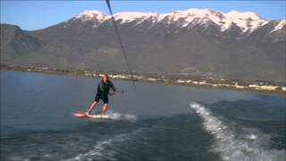 Slow motion shot of a smililng wakeboarder as he does a variety of stunts