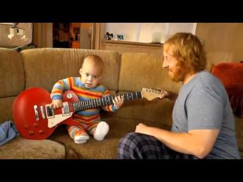 Un bébé joue de la guitare