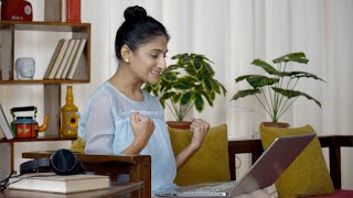 Indian woman working and typing on a laptop - Excited with good news