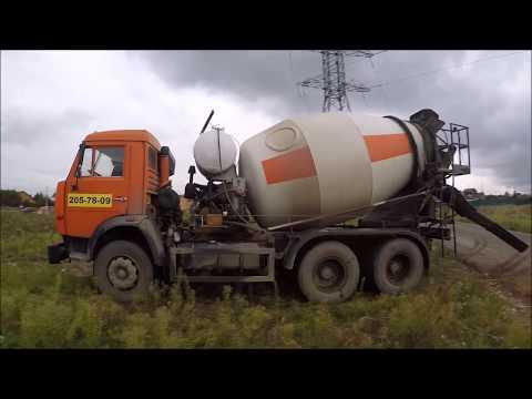 Груженый бетоном Камаз - миксер маневрирует в поле