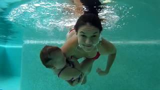 Мама с дочкой ныряют с бассейне