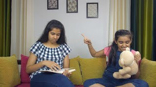 Cute little girl irritating her beautiful elder sister while sitting on a couch - Two sisters of India
