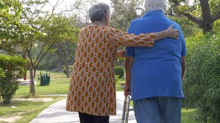 Back view shot of an old couple doing morning walk together in a hospital park