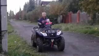 Ребенок катается на квадроцикле с папой