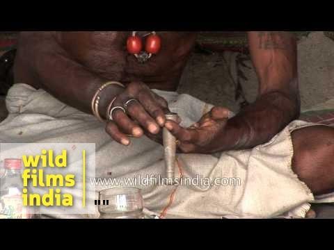 Aghori baba filling a chillum with marijuana