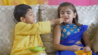 Cute Indian boy feeding french fries to his sister on Raksha Bandhan festival