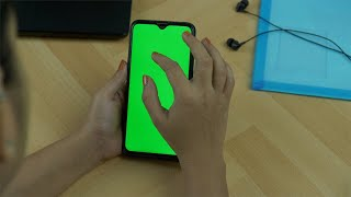 Closeup shot of woman hands using her green mock-up screen smartphone at office