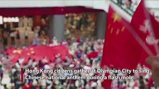People in Hong Kong chorus national anthem during flash mob