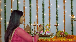 Pretty Indian lady performing Hindu traditions of worshipping Lakshmi and Ganesh on Diwali