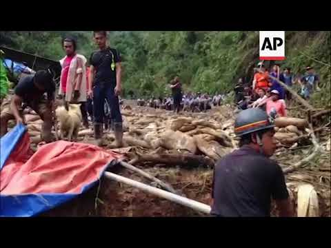 Ground shots of rescuers searching through mud of Philippines landslide