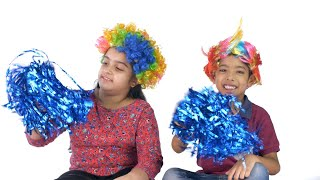 Cheerful Indian kids in fancy colorful wigs playing with pom-poms - casual wear