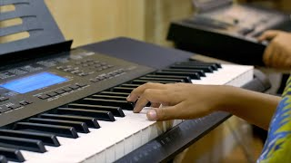 An Indian boy playing piano in a music studio