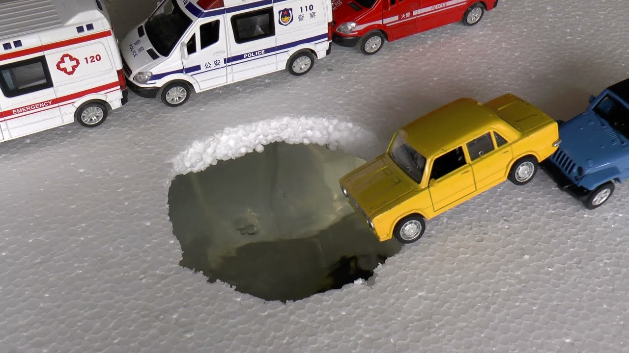 Toy diecast model cars fall into a hole with water