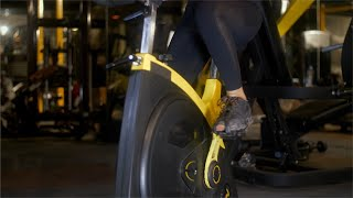 Tilt shot of a young female athlete riding a stationary bicycle at the fitness club