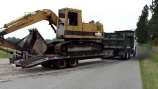 Tandem dumptruck hauling excavator on tag trailer