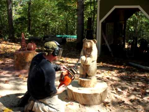 Chainsaw carving a small brown bear, by Mark Poleski