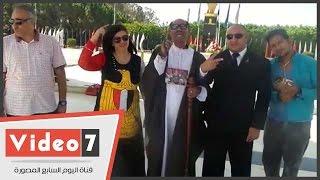 سيدة ترتدى علم مصر ومواطنون يحتفلون بعيد تحرير سيناء أمام النصب التذكارى