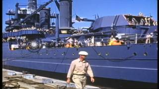 Dock hands at work and crew on the deck of USS California (BB-44) departing Pearl...HD Stock Footage