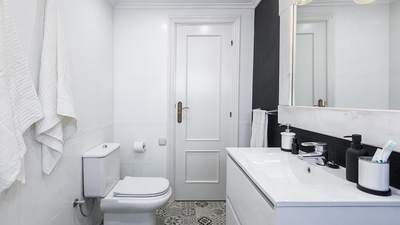 Cuarto de baño en blanco y negro elegante y luminoso sin ...