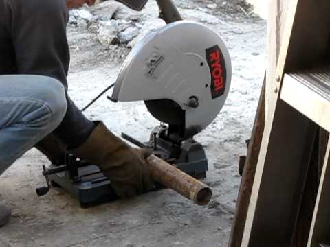 Hubby using a metal Cut-Off Chop-Saw on a metal-fence-pole